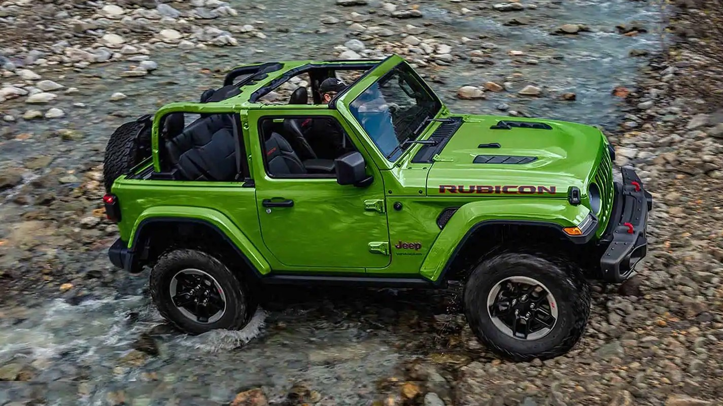 A green 2019 Jeep Wrangler with no top driving through a rocky river