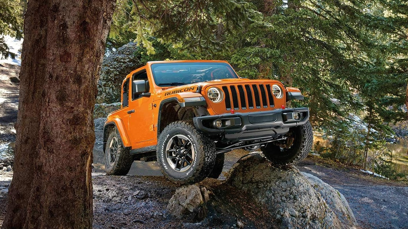 An orange 2019 Jeep Wrangler with no top climbing over a rock in the forest